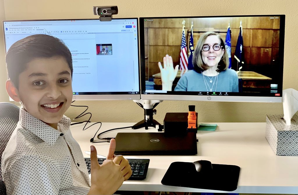 Taneesh sits at a desk with a monitor showing Kate Brown on video chat.