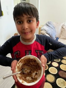 A boy holding a bowl with chocolate hummus inside