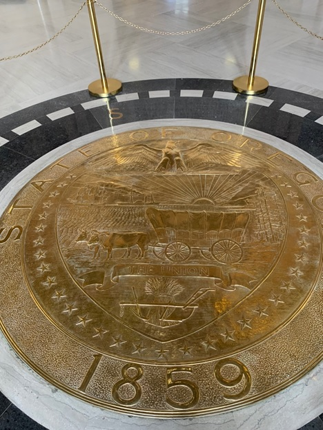 Gold Oregon state seal emblem in the middle of the Rotunda floor at the capitol.