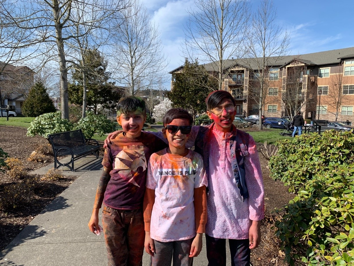 Three children covered in red and orange paint after playing Holi