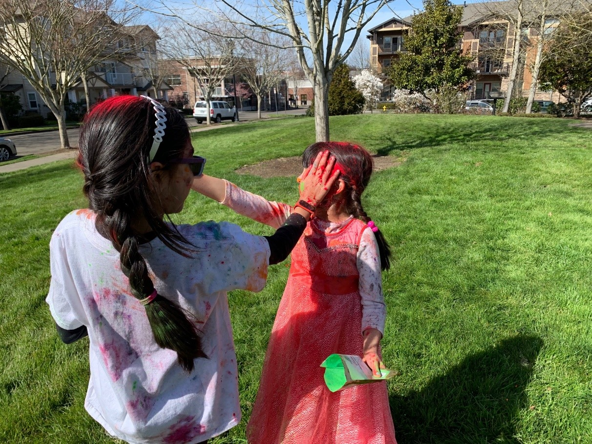 Two children putting colors on each other during Holi