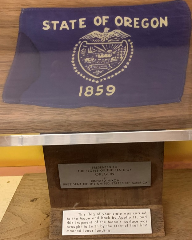 State of Oregon flag with plaque reading: This flag of your state was carried to the Moon and back by Apollo 11, and this fragment of the Moon's surface was brought to Earth by the crew of that first manned lunar landing.