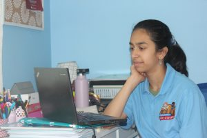 Raaga sitting at desk in front of laptop.