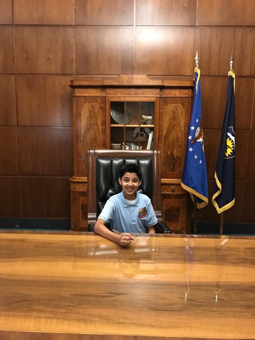 Taneesh sits at the Governor's ceremonial desk. He has a pen in his hand.