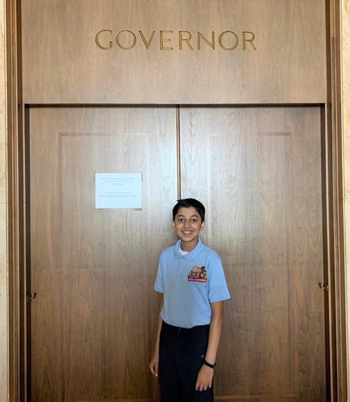 """Taneesh stands in front of a set of doors with the word """"Governor"""" carved overhead."""