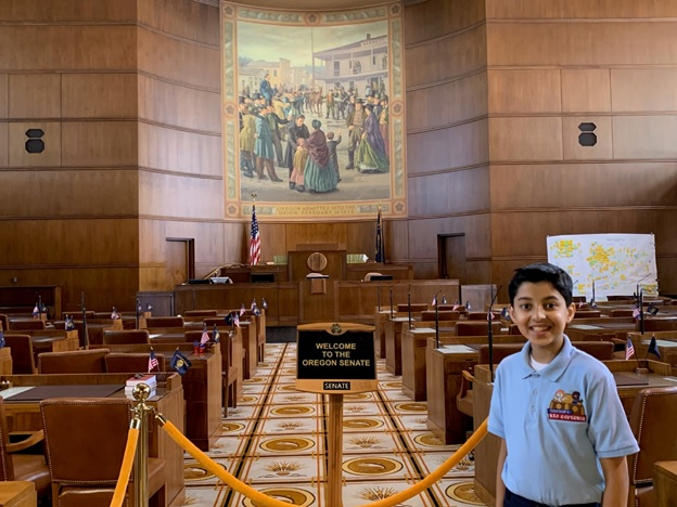 Taneesh stands on the Oregon Senate floor with a mural in the background.