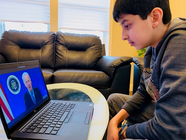 Taneesh watches President Biden speak on a laptop