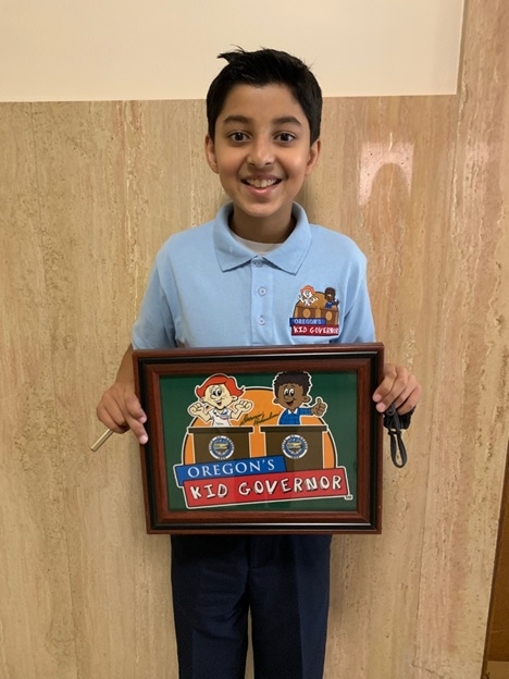 Taneesh stands and holds a sign of the Kid Governor logo.